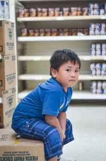 boy wearing blue crew neck t shirt sitting on cardboard box
